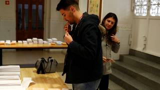 People pick up ballots as they prepare to vote during general election in Madrid, Spain, November 10, 2019.