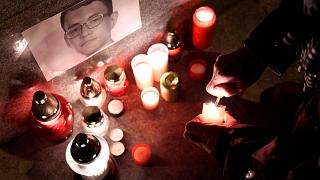 A journalist lights a candle in memory of murdered investigative journalist Jan Kuciak, in Trencin, Slovakia, February 26, 2018.