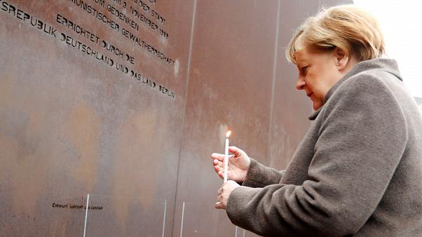 German Chancellor Angela Merkel lights a candle at the memorial of the divided city and the victims of communist tyranny