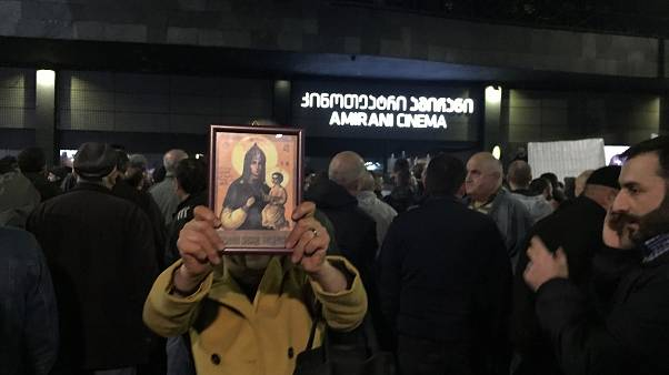 """A woman holds a religious icon as she protests against the screening of """"And Then We Danced"""", a Georgian movie about gay love in Tbilisi, Georgia"""