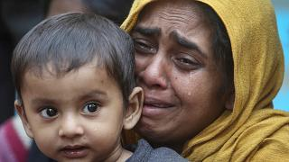 FILE PHOTO: A Rohingya Muslim woman cries as she holds her daughter after they were detained by Border Security Force (BSF) soldiers while crossing the India-Bangladesh border