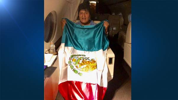 Former Bolivian President Evo Morales holds a Mexican flag onboard a Mexican government's aircraft in an unidentified location  November 11, 2019