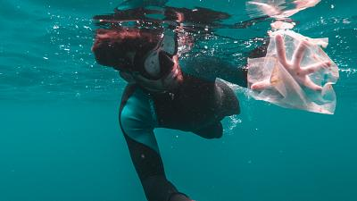 A diver captures plastic waste floating in the ocean.