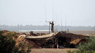 soldato israeliano al confine con gaya a sud d'Israele mentre regola il sistema di comunicazione