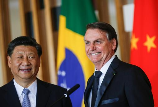 Brazil's President Jair Bolsonaro reacts next to China's President Xi Jinping as they deliver a joint statement after a bilateral meeting during the BRICS summit in Brasilia