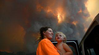أم وطفلها ينظران إلى سحب دخان النيران الكثيف يتصاعد من الغابات المحترقة بالقرب من نانا غلين - 2019/11/12 -