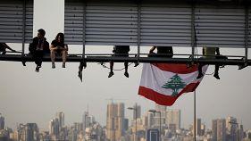 متظاهرون يجلسون على لافتة على طريق مظاهرة تسد الطريق السريع خلال الاحتجاجات المستمرة المناهضة للحكومة في الحازمية، لبنان 13 نوفمبر/ تشرين الثاني 2019