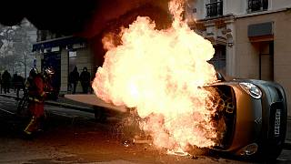 A firefighter tries to extinguish a burning car on place d'Italie in Paris on November 16, 2019
