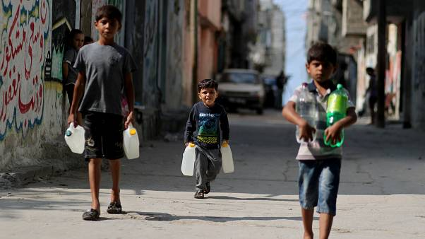 فتيان فلسطينيون يحملون زجاجات مياه أثناء سيرهم في مخيم الشاطئ في مدينة غزة