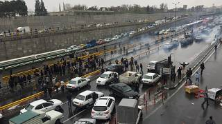 People stop their cars in a highway to show their protest for increased gas price in Tehran, Iran