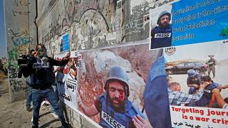 صحفيون فلسطينيون يضعون ملصقات تظهر زميلهم معاذ العمارنة الذي أصيب بعيار ناري في عينه تضامنا معه في بيت لحم في الضفة الغربية