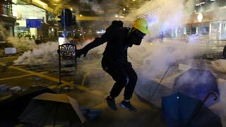 A protester runs from tear gas during clashes with riot police at Tsim Sha Tsui, in Hong Kong, China, November 18, 2019.