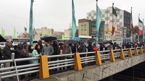 People stands in the street to show their protest against increased gas price in Tehran
