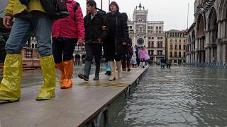 Tourists walk in St. Mark's Square after days of severe flooding in Venice, Italy, November 17, 2019.