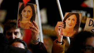 People carry photos of assassinated anti-corruption journalist Daphne Caruana Galizia during an anti-corruption protest against the government of Prime Minister Joseph Muscat,