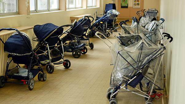 FILE PHOTO: Pushchairs are parked at the entrance of a day-nursery in Vincennes, near Paris, April 30, 2003.