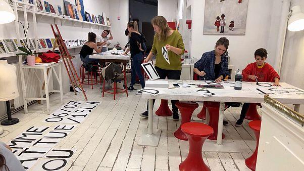 ناشطات وناشطون في فرنسا يصنعون ملصقات مناهضة للعنف المنزلي ضد المرأة