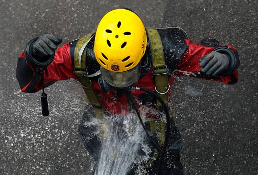 A rescue diver from the Fire Service department is rinsed after entering the sewage system to search anti-government protesters