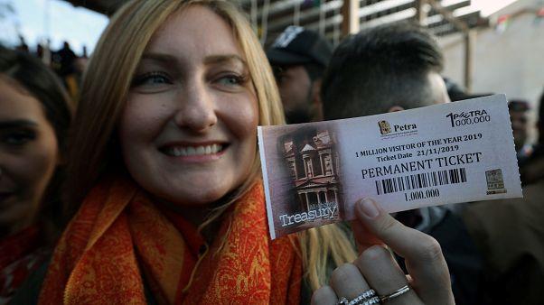 السائحة الأميركية أليسون كيري تحمل بطاقة رقم مليون لتتم رقم مليون سائح زاروا مدينة البتراء بالأردن في العام 2019. 21/11/2019