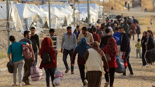 Syrian displaced families, who fled violence after the Turkish offensive in Syria, are seen upon arrival at a refugee camp in Bardarash on the outskirts of Dohuk, Iraq October