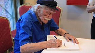 Ο Μανώλης Γλέζος υπογράφει το βιβλίο το «ΑΚΡΩΝΥΜΙΑ»