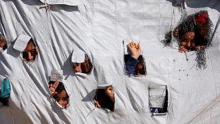 أطفال ينظرون من ثقوب في إحدى خيام مخيم الهول بمحافظة الحكسة السورية. 02/04/2019