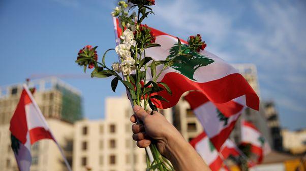 """لبنانية ترفع علم لبنان وباقة من الزهور خلال """"الاحتفال المدني"""" بعيد الاستقلال السادس والسبعين في بيروت"""
