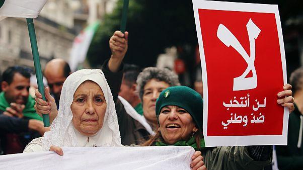 إمرأة جزائرية ترفع ملصقا في الجزائر العاصمة- أرشيف رويترز
