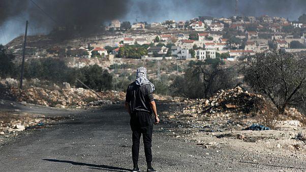 فلسطيني يقف أمام مستوطنة كدوميم بالقرب من الضفة الغربية- أرشيف رويترز