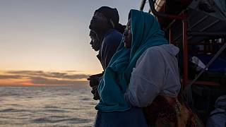 Some of the people onboard the Aita Mari look at the island of Sicily