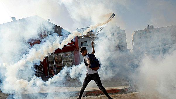 متظاهر فلسطيني يعيد قنبلة الغاز بالقرب من مستوطنة بيت إيل، الضفة الغربية- أرشيف رويترز