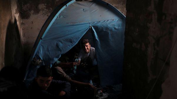 Migrantes de Afganistán sentados en su tienda de campaña en una imprenta abandonada cerca de la frontera croata, cerca de la ciudad de Sid, Serbia, el 4 de septiembre de 2019.
