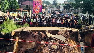 Des habitants de Kinshasa, devant une route coupée en deux.