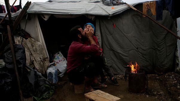لاجئ سوري يعانق ابنه بالقرب من خيمة للجوء في اليونان