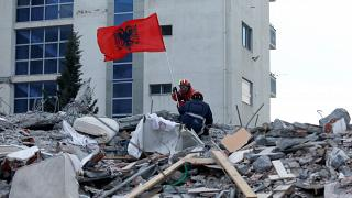 Rescue workers marked Albania's Flag Day by flying a flag above the rubble of a quake-collapsed building in Durres.
