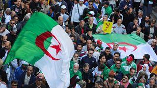 صورة لمتظاهرين يحملون أعلام ولافتات تعبر عن رفضهم للانتخابات الرئاسية في العاصمة الجزائرية