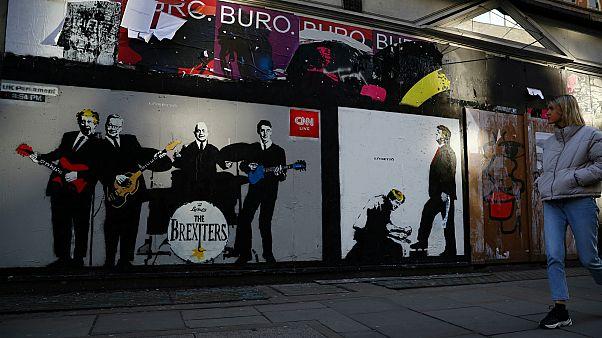 مشاة في لندن بجانب غرافيتي جرافيتي  بوريس جونسون ونائب حزب المحافظين والرئيس الأمريكي دونالد ترامب- أرشيف رويترز