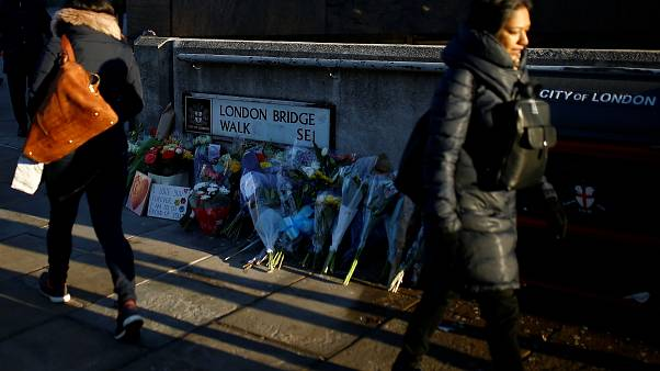 Commuters walk past flowers and signs left at the scene of a fatal attack on London Bridge in London, Britain December 2, 2019.