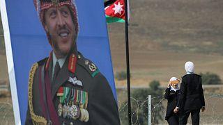 شرطيات أردنيات يلتقطن صوراً بجوار ملصق للعاهل الأردني الملك  عبد الله الثاني