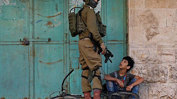 جندي إسرائيلي يحتجز طفلاً فلسطينياً خلال مظاهرة مناهضة لإسرائيل في الخليل بالضفة الغربية المحتلة من قبل إسرائيل- 29/11/2019