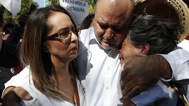 Julián LeBarón abraza a dos mujeres durante la protesta por el aniversario de la presidencia de López Obrador