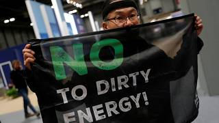 An activist protests as part of the Make Big Polluters Pay campaign inside the venue of the U.N. climate change conference (COP25) in Madrid, Spain, December 4, 2019