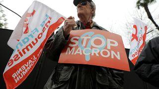 """متظاهر في فرنسا يحمل لافتة كتب عليها """"أوقفوا ماكرون"""""""