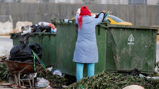 امرأة تجمع قارورات البلاستيك من صندوق للقمامة في تونس