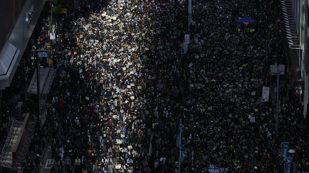 Pro-democracy protesters march on a street in Hong Kong, Sunday, Dec. 8, 2019.
