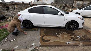 رجل فلسطيني يتفقد إطارات سياراته التالفة بعد عمليات تخريبية لعربات فلسطينيين في القدس