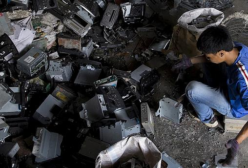 Worker recycles CD players at a workshop in the township of Guiyu in China's southern Guangdong province June 9, 2015