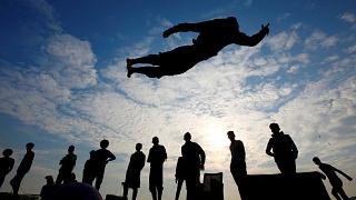 Iraqi demonstrators perform a somersault as they practice parkour during ongoing anti-government protests, near the Tigris River in Baghdad, Iraq. December 9, 2019.