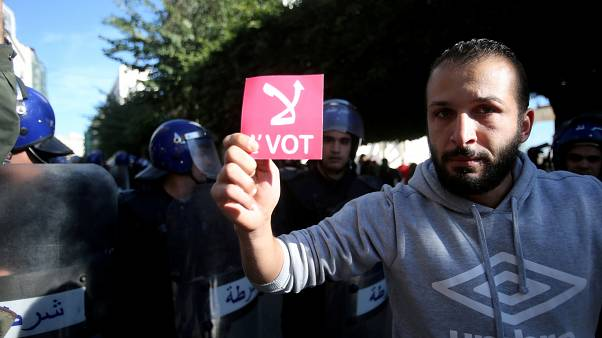 A demonstrator holds a card during a protest calling to reject the upcoming presidential election in Algiers, Algeria December 11, 2019.