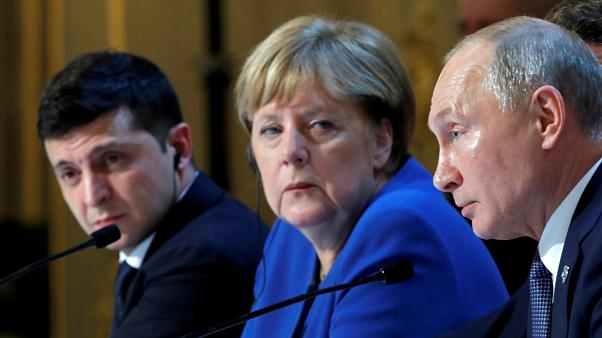 Ukraine's Volodymyr Zelenskiy, Germany's Angela Merkel and Russia's Vladimir Putin attend a joint news conference after summit in Paris on December 10, 2019.